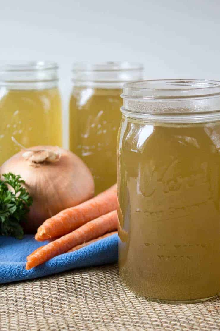 Homemade Chicken Broth in quart sized canning jars.