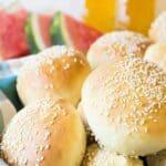 A basket full of hamburger buns with sesame seeds.