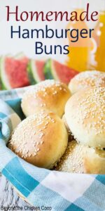 A basket filled with sesame seed topped buns.