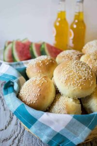 A basket lined with a blue and white napkin filled with sesame seed hamburger buns.