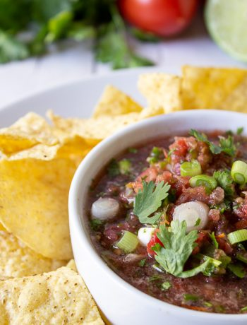 Salsa topped with sliced onions and fresh cilantro.