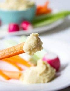 A carrot stick with a hummus on the end.