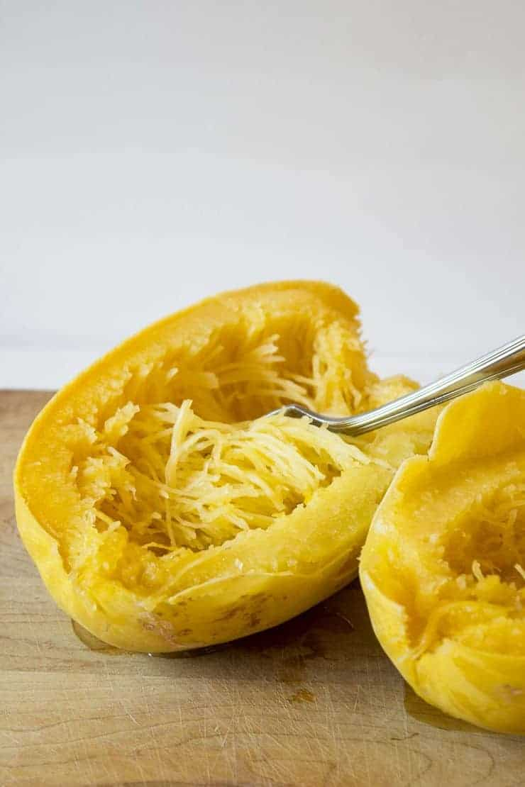 Spaghetti Squash halved with strands of squash fluffed with a fork.