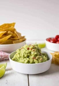 A white bowl piled with green guacamole with small bits of chopped tomatoes.