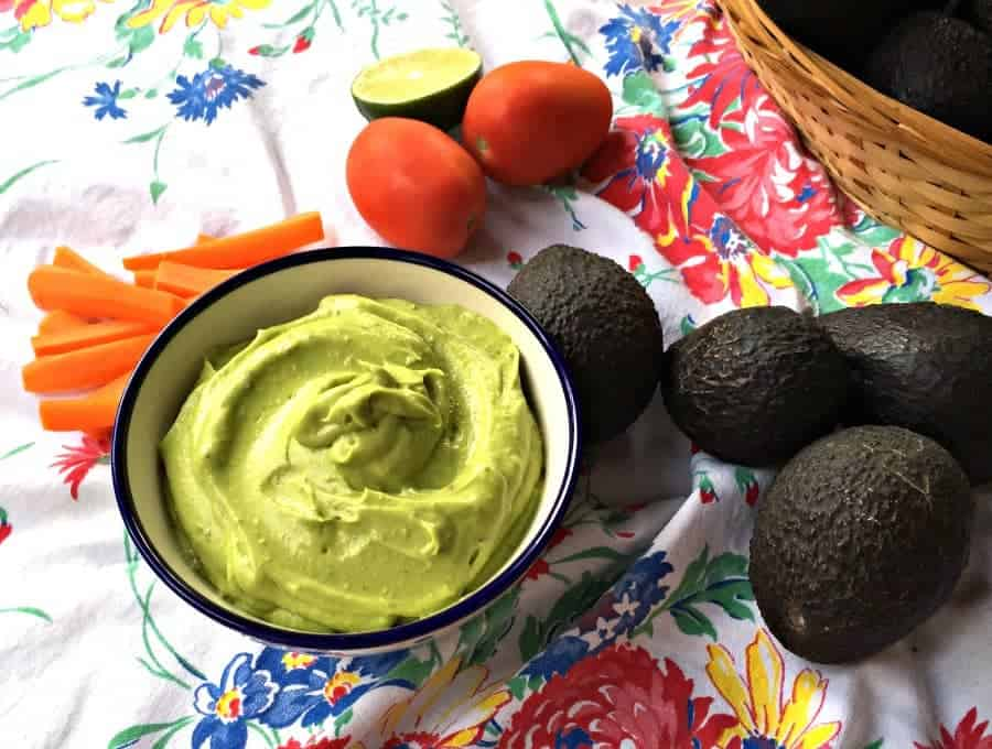 Green avocado dip with sliced carrots next to the bowl.