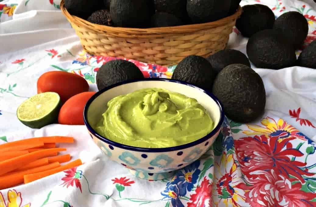 Avocado dressing in a patterned bowl with fresh veggies and avocadoes around the bowl.