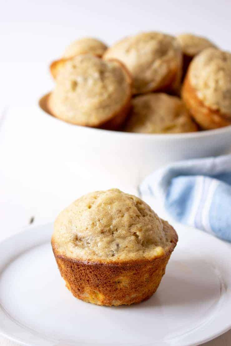 A tan muffin sitting on a white plate with a bowl of muffins in the background.