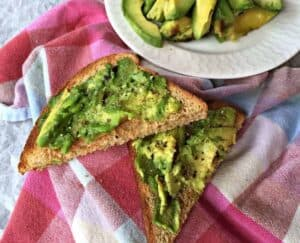 Smashed avocadoes on pieces of toast.