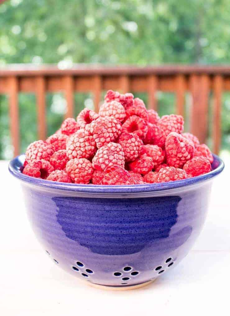 A blue colander filled with frozen raspberries.