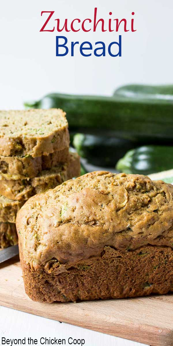 A loaf of zucchini bread with fresh zucchini behind the loaf of bread.