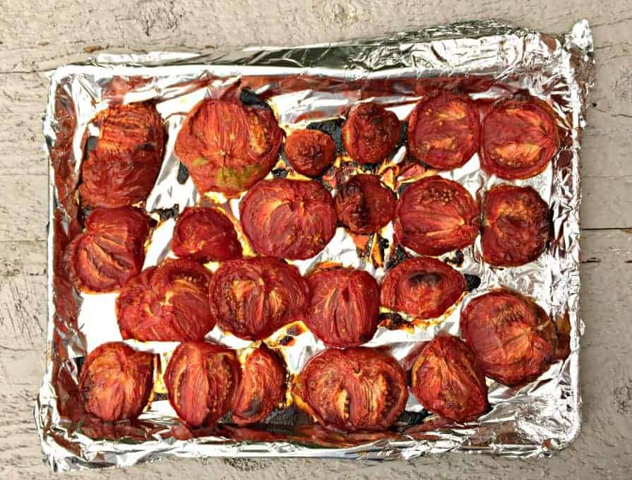 Oven roasted tomatoes on a foil lined baking sheet.