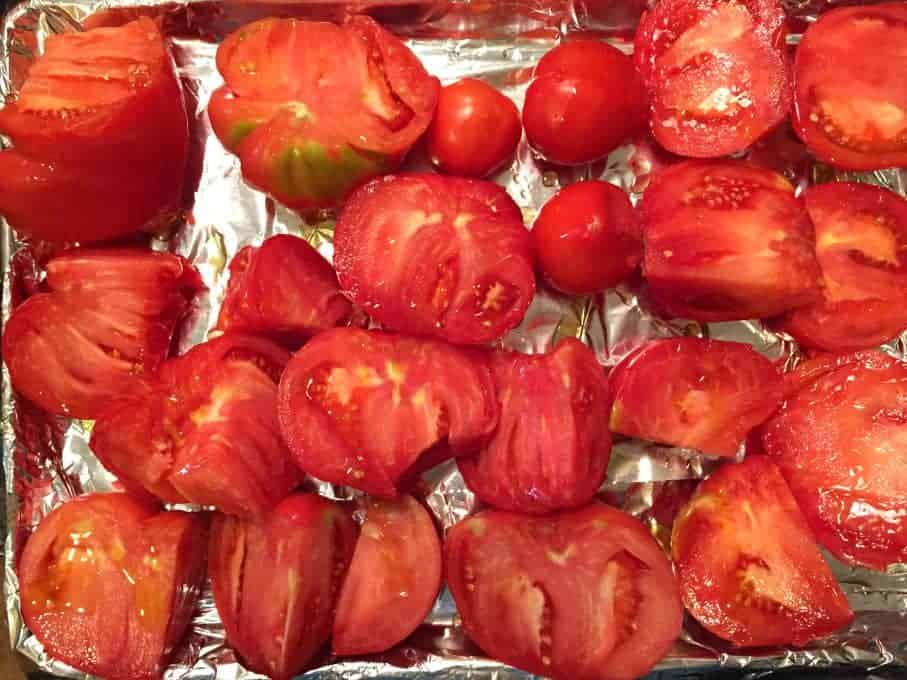 Tomatoes with olive oil on a foil lined baking sheet.