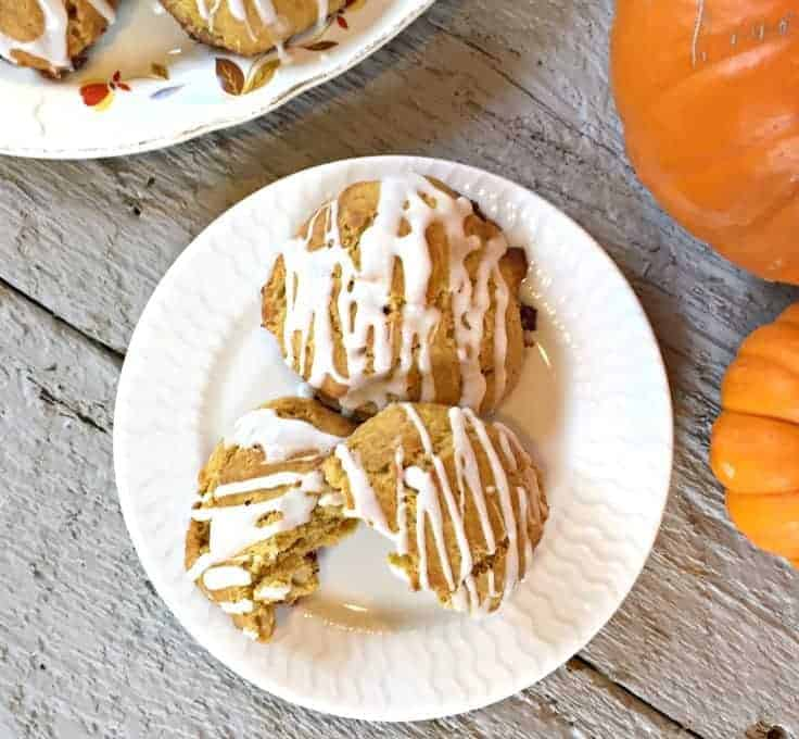 Three pumpkin scones with a drizzle of a white glaze across the top.