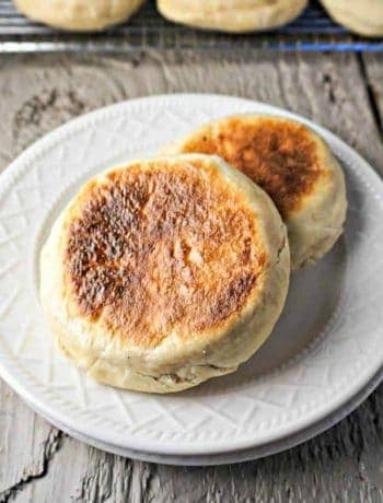 Two browned english muffins on a plate.