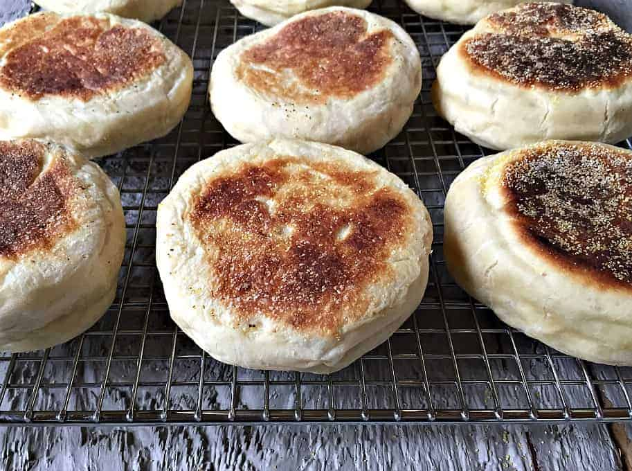 Homemade English Muffins cooling on a baking rack.