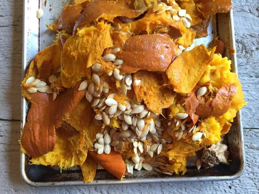 Pumpkin skins and seeds on a baking sheet.