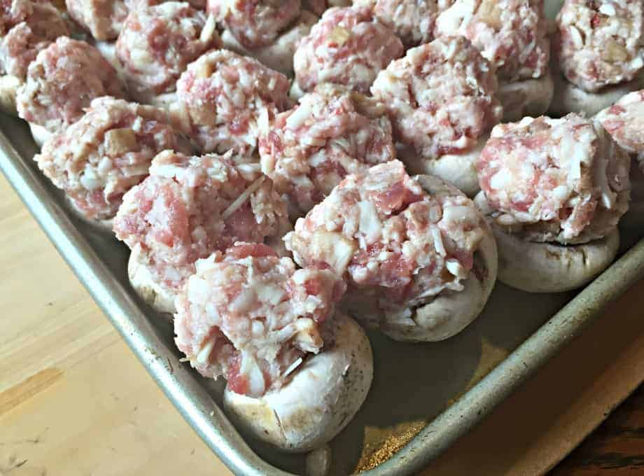 Mushrooms filled with sausage and cheese on a baking sheet.
