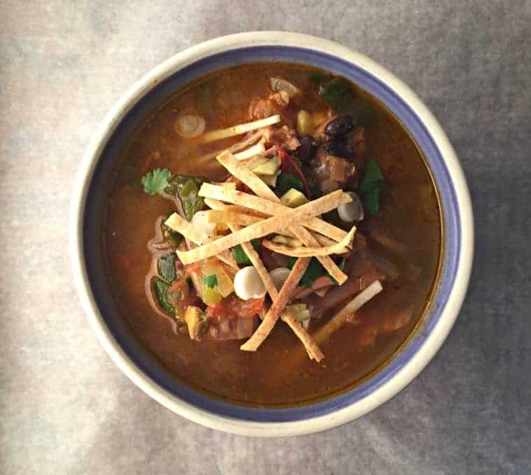 An overhead shot of a bowl of soup topped with tortilla strips.