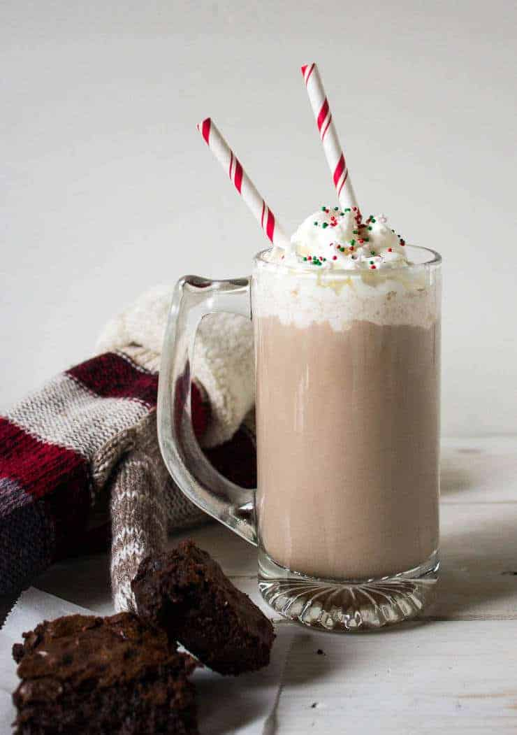Tall glass mug filled with hot chocolate and topped with whipped cream.