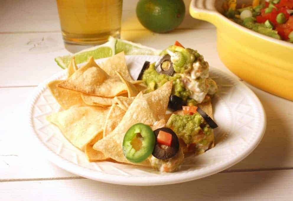 Mexican layered dip with beans and guacamole served on corn chips