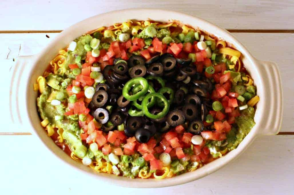 Mexican layered dip with beans and guacamole.