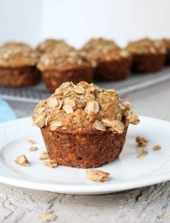 Oatmeal Banana Muffin on a small white plate with crumb topping crumbled on plate.