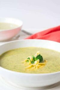 A bowl full of creamy soup topped with cheese and a broccoli floret.