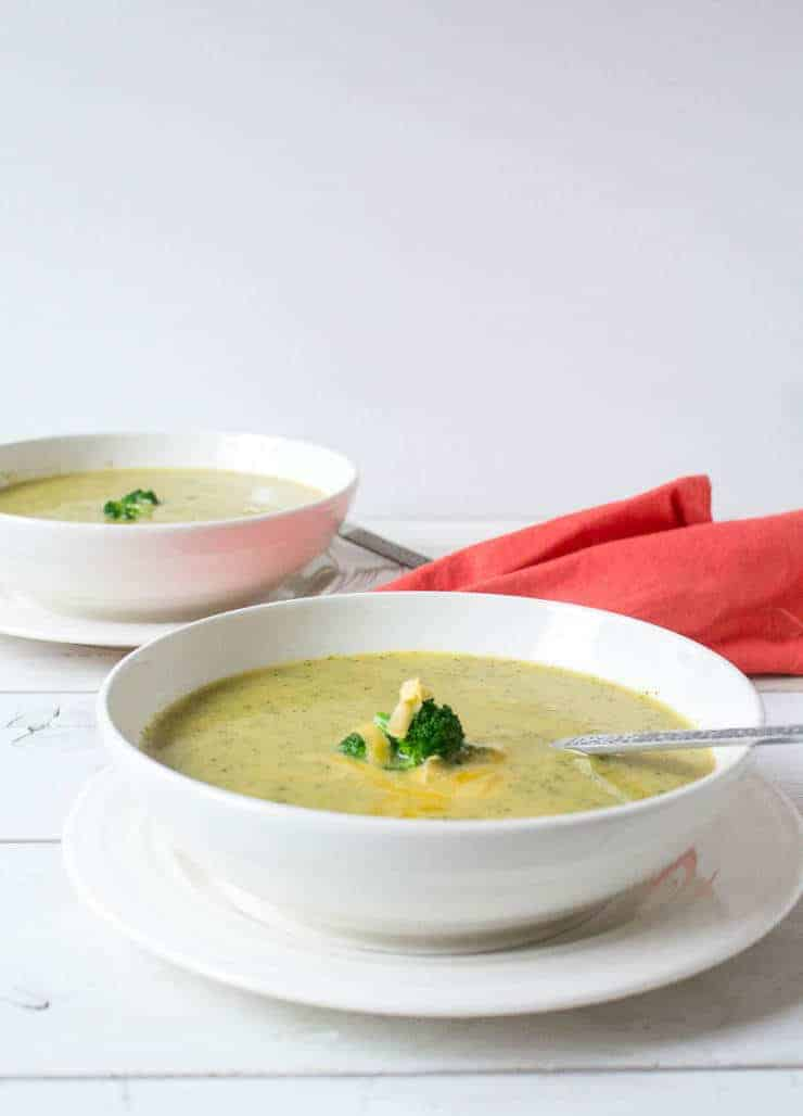 A bowl of soup with broccoli and cheese.