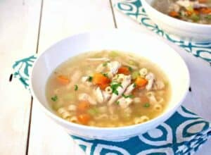 A white bowl filled with a clear broth with carrots, chicken and pasta.