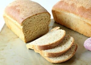 Two loaves of homemade bread with one loaf partially sliced.