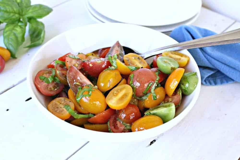 Heirloom Tomato salad is quick, easy and delicious. A light dressing brings out the very best flavor of fresh tomatoes. -Beyond the Chicken Coop