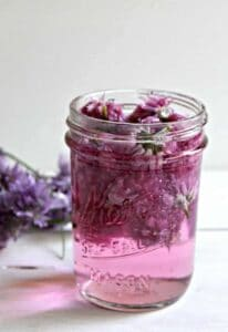 A glass jar filled with a purple vinegar and chive blossoms.