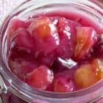A glass jar filled with cherries in a sauce.