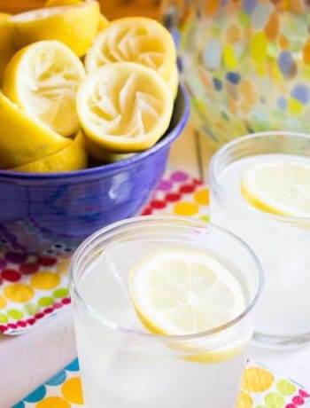 A glass jar filled with lemonade and a lemon slice.