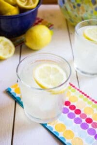 A glass filled with lemonade on top of a colorful napkin.