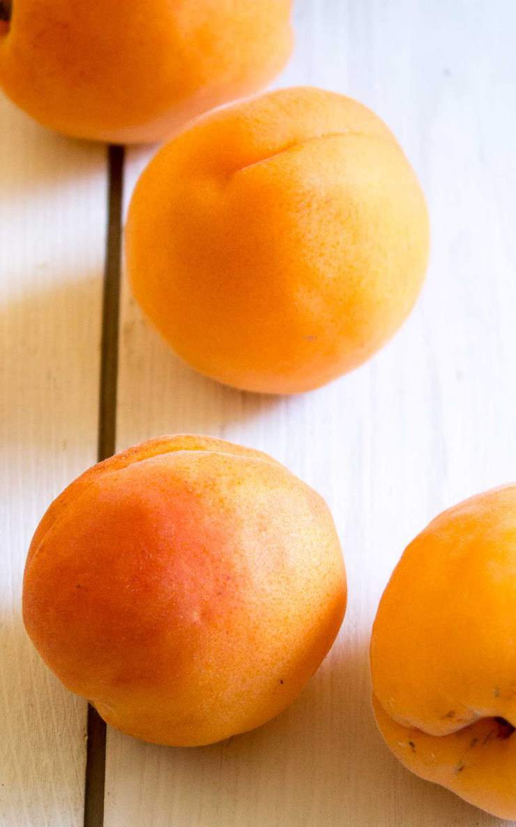 Fresh Apricots on a white board.