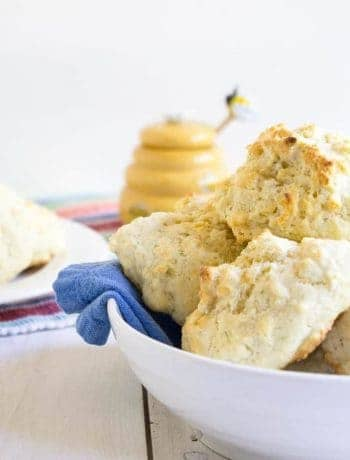 A white bowl with a blue napkin filled with biscuits.