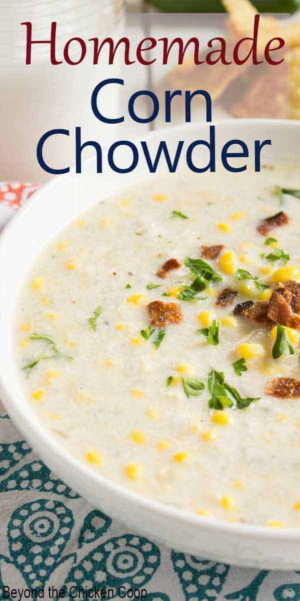 A bowlful of chunky corn chowder topped with bacon.