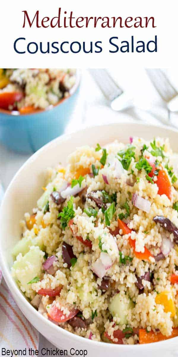 A white bowl filled with a couscous salad and fresh veggies.