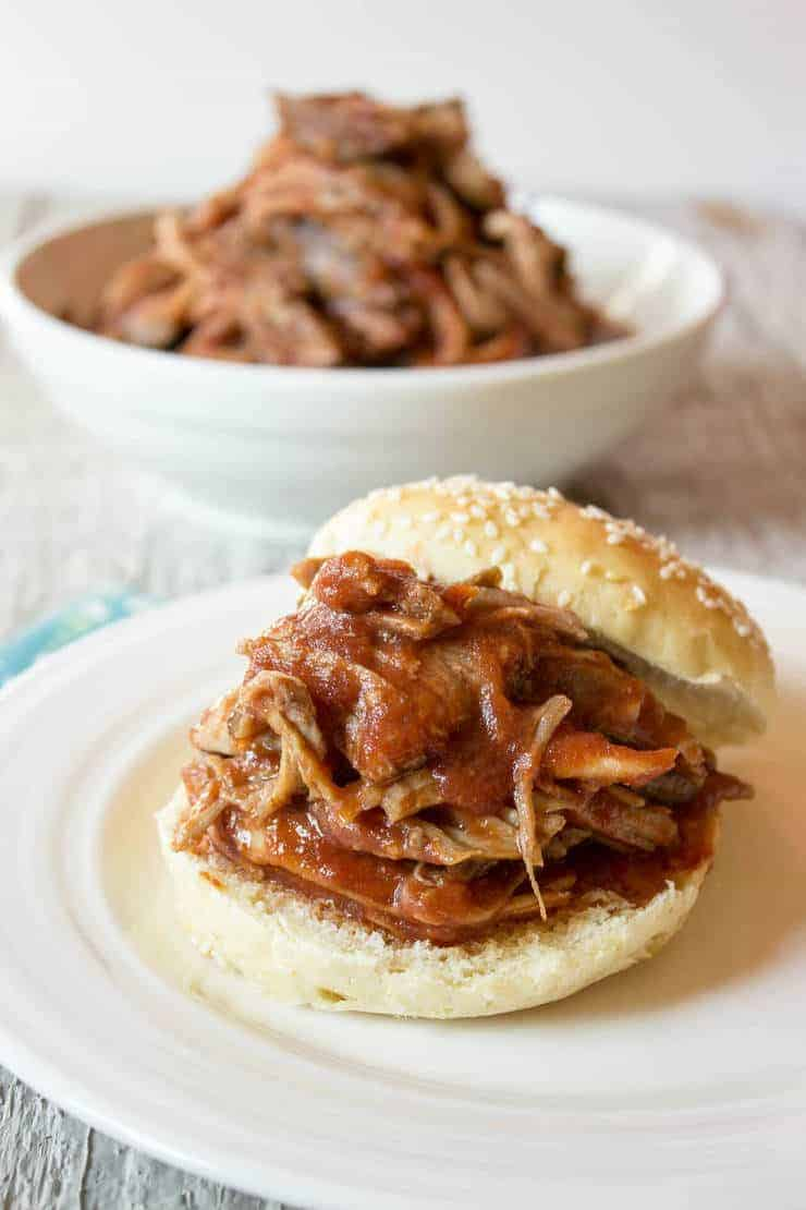 A bun pilled high with pulled pork made in the crock pot. Barbecue sauce is poured over the pork.