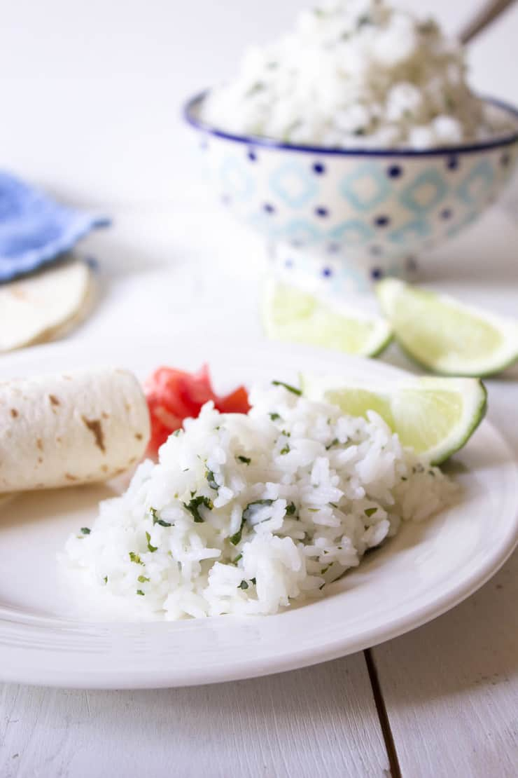 A white plated filled with rice, limes and tortillas.