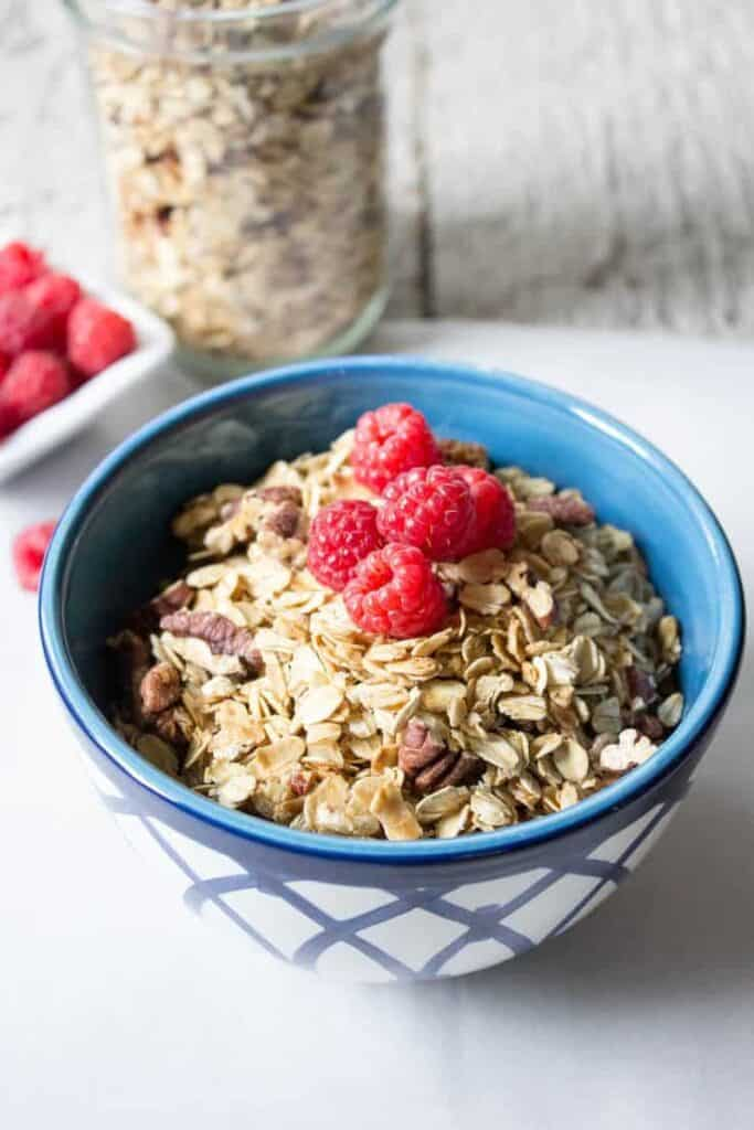 A bowlful of Maple Pecan Granola topped with fresh raspberries.