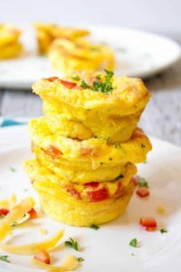 A stack of three mini egg cups filled with cheese, ham and veggies.