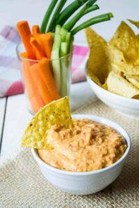 A bowl with bell pepper hummus with a chip sticking out of the hummus.