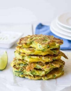 A stack of zucchini fritters on a white surface with a blue napkin behind the stack.