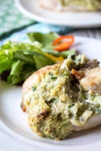 Chicken breast stuffed with zucchini and cheese on a white plate.