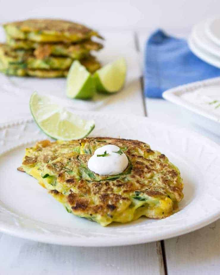 A zucchini pancakes on a plate with a dollop of white cream and fresh cilantro.