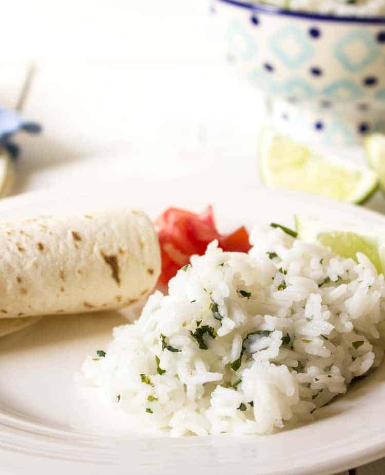 White rice with bits of fresh herbs on a plate with a tortilla and tomatoes.