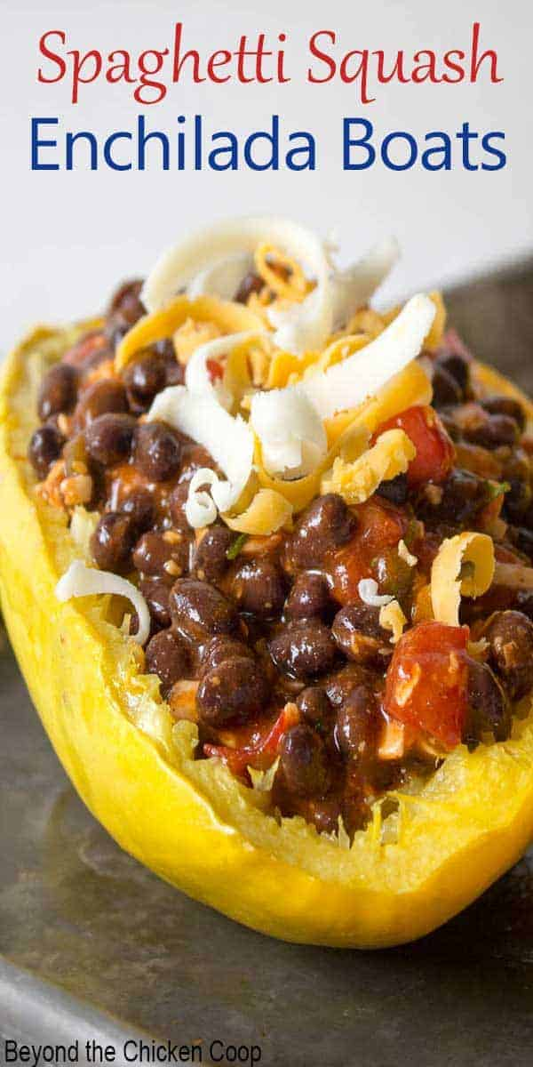 Half of a spaghetti squash filled with black beans and enchilada sauce.