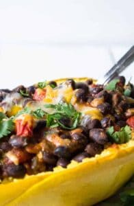 Half a spaghetti squash shell filled with black beans, tomatoes and cheese.